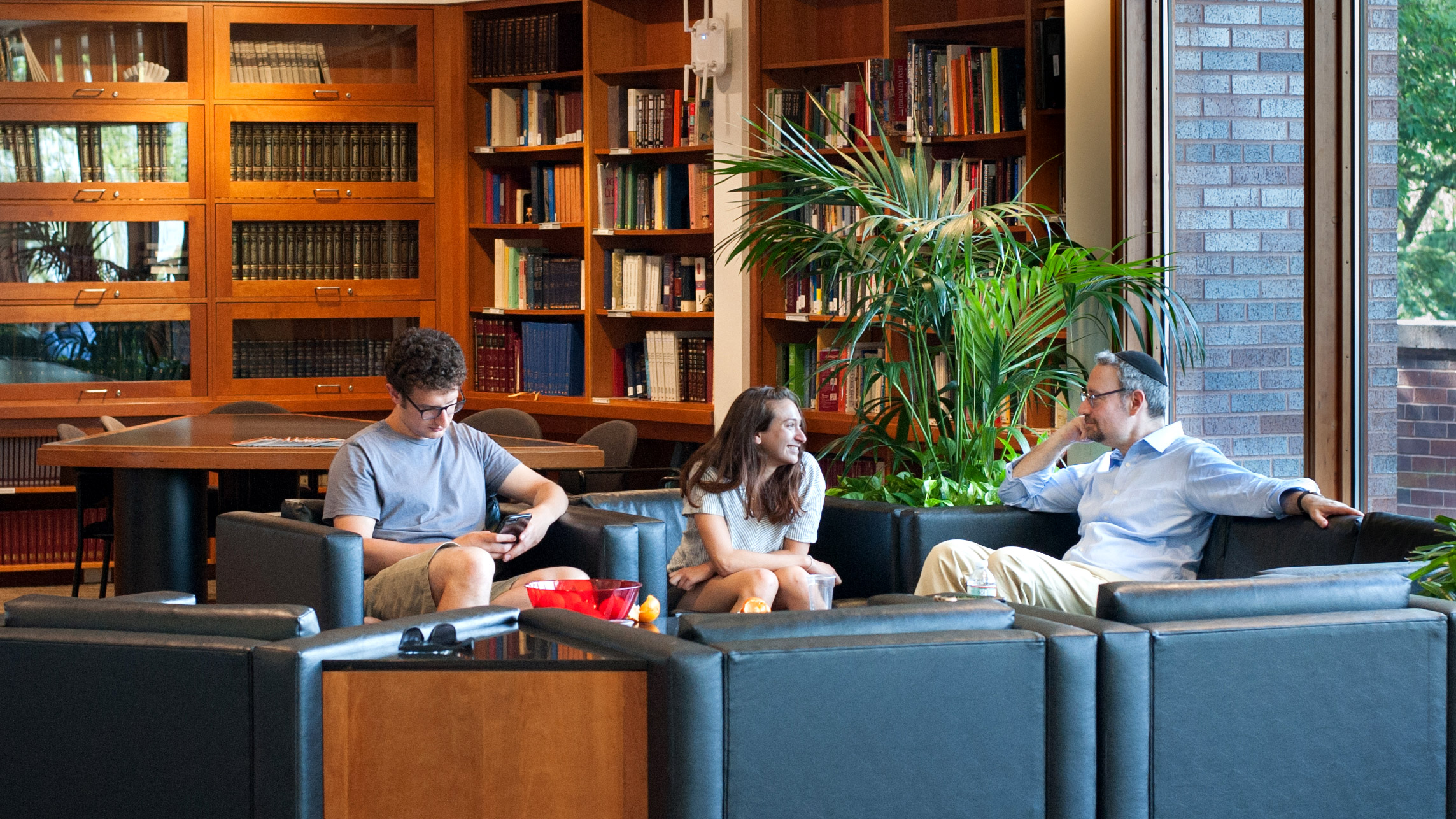 Students sit near library with Rabbi Brawer